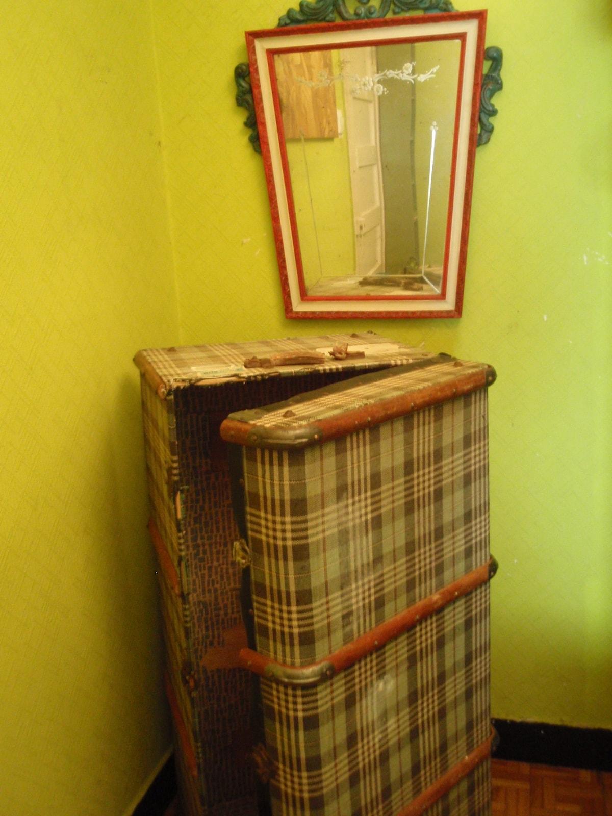 Baúl trans-oceánico, reconvertido en armario para el viajero y espejo veneciano antiguo.