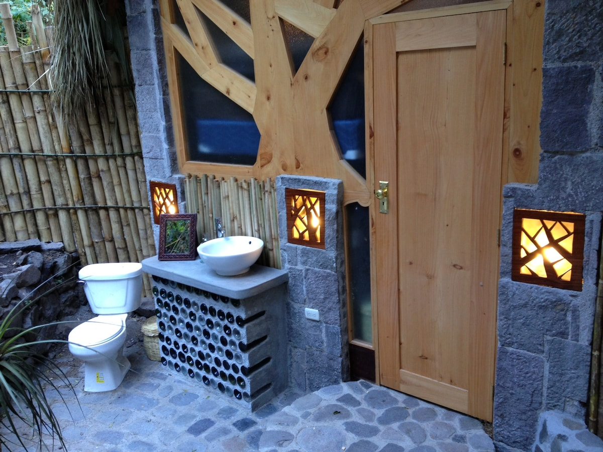 Standard bungalow bathroom with recycled wine bottles in the vanity.  Gorgeous lush garden spa bathroom with rain shower.