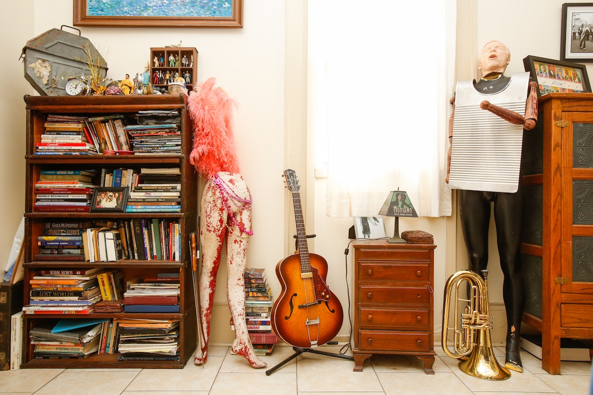 Books, instruments, mannequins, and what nots in the dining room / music room.