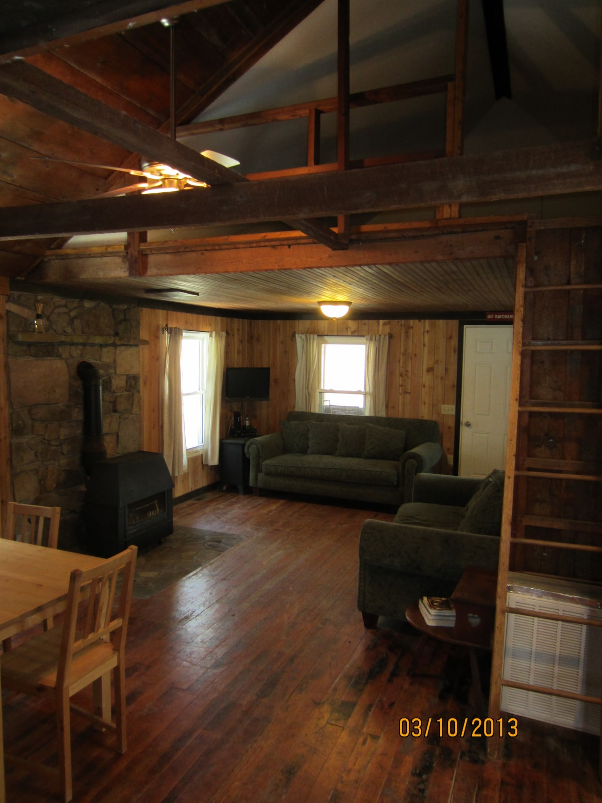 Living room with wood burning stove and loft (up the ladder).