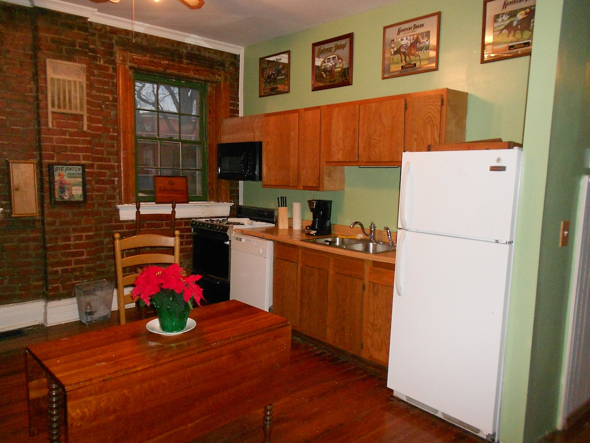 KITCHEN WITH EXPOSED BRICK WALL, CHERRY DINING TABLE