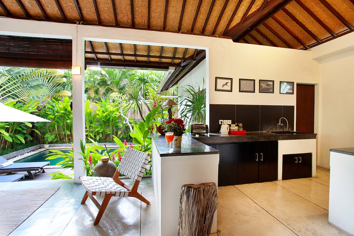 Equipped kitchen with a sweeping view of the pool & garden