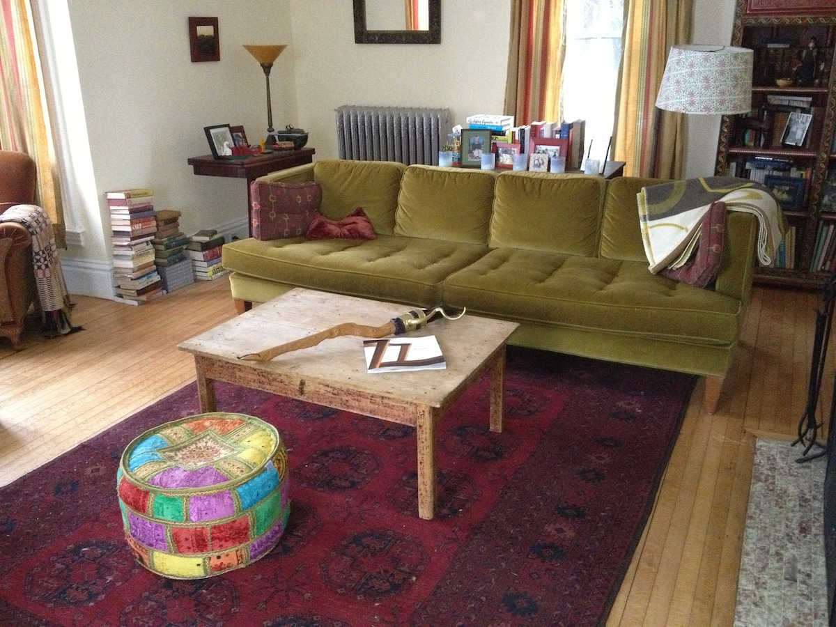 The formal living room. Working fireplace, bay window, great couch for a nap and tons of books.