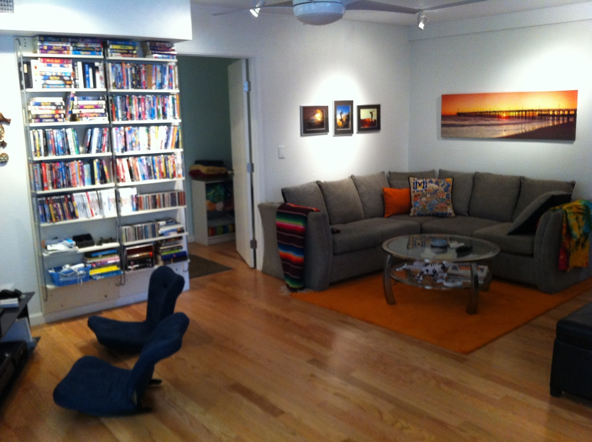 The den has a sectional with a hide a bed, local surf art, blankets and lots of games and movies - including video games and toys