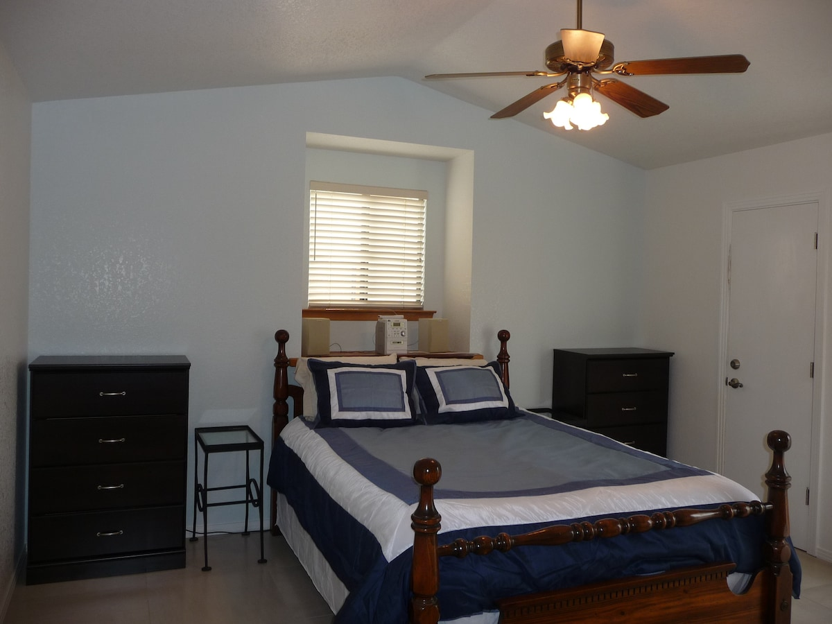 Master bedroom upstairs with queen bed and door to balcony.