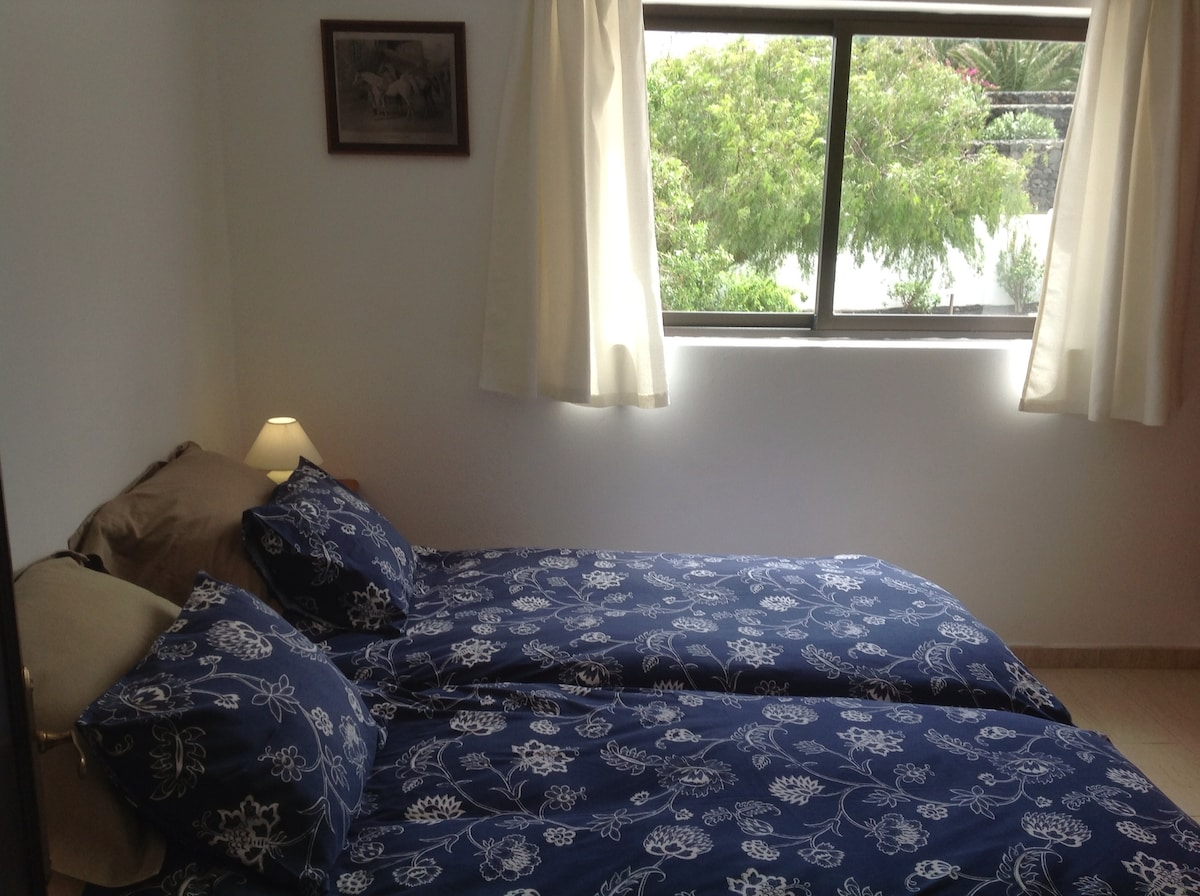 First floor apartment with twin beds and view of the garden
