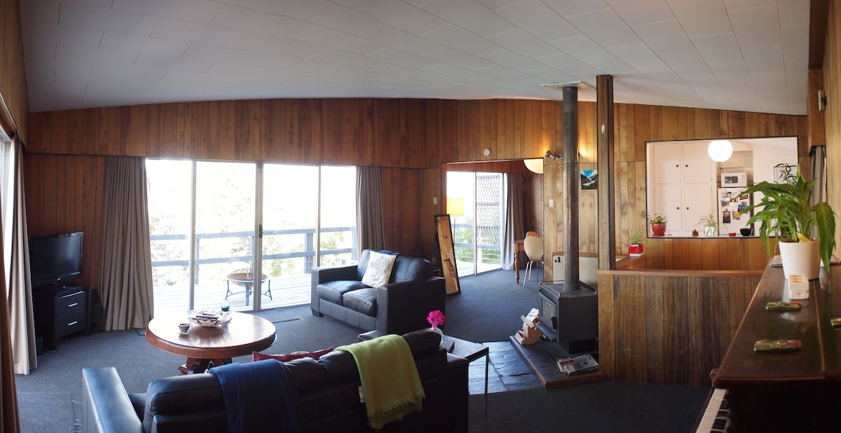 Big open living area with wood burner opening to deck, dining area and kitchen