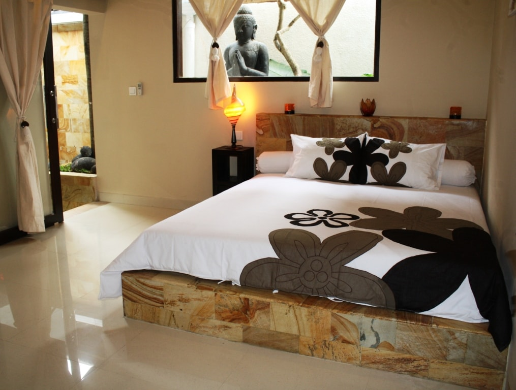 The bedroom with large Buddha statue in the outdoor garden bathroom.