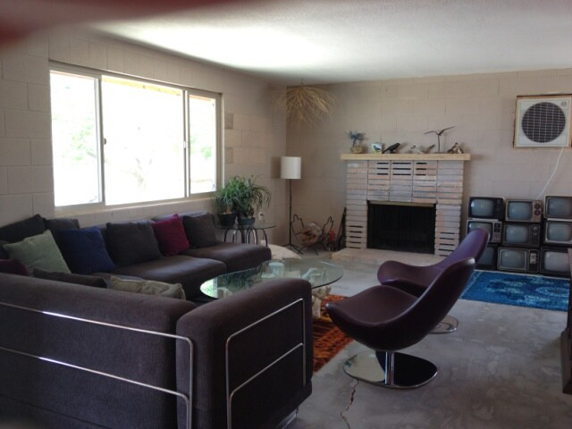 Living room with wood burning fireplace and old TV collection. Swamp cooler in wall cools house down quickly.