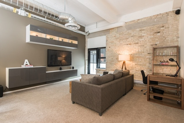 Living room with 12 ft. tall ceilings, exposed brick, luxurious furnishings, and a 60 inch TV