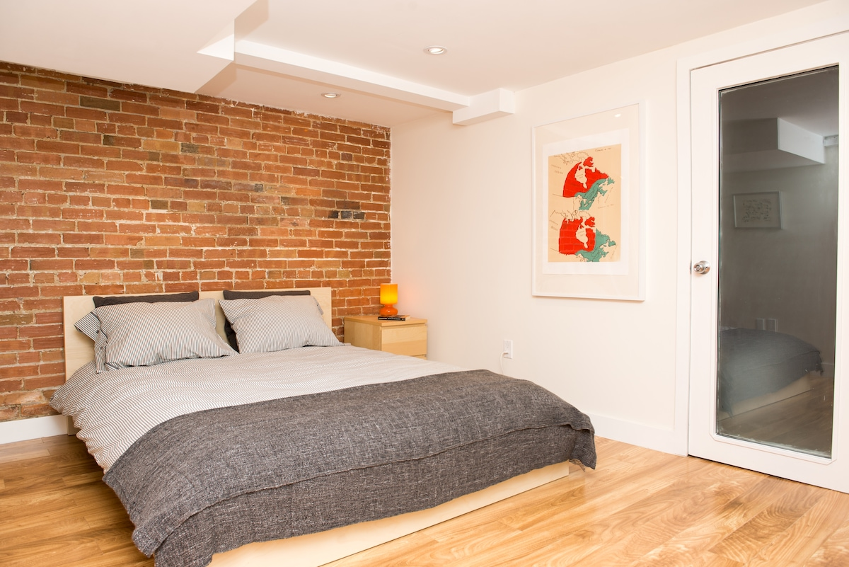 Queen size memory foam bed and stunning exposed brick.