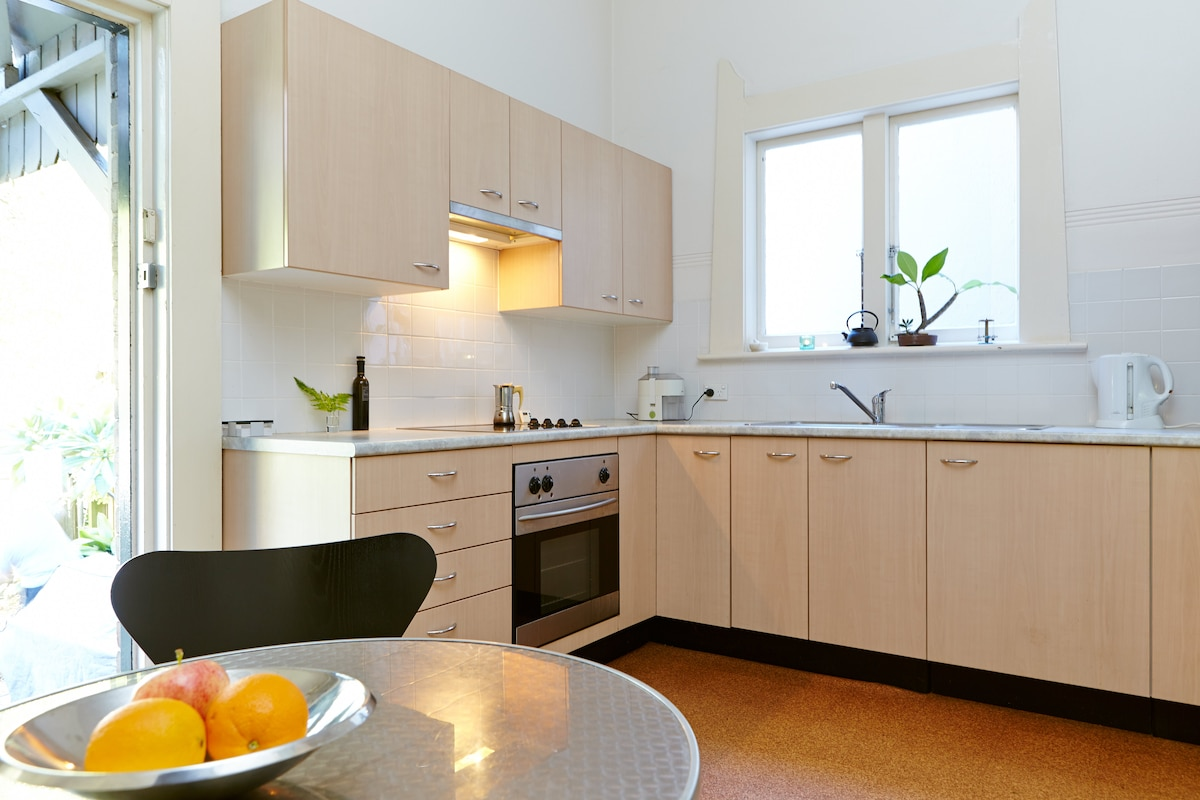 The kitchen, opening onto the garden, has a private guest fridge and adjacent laundry.