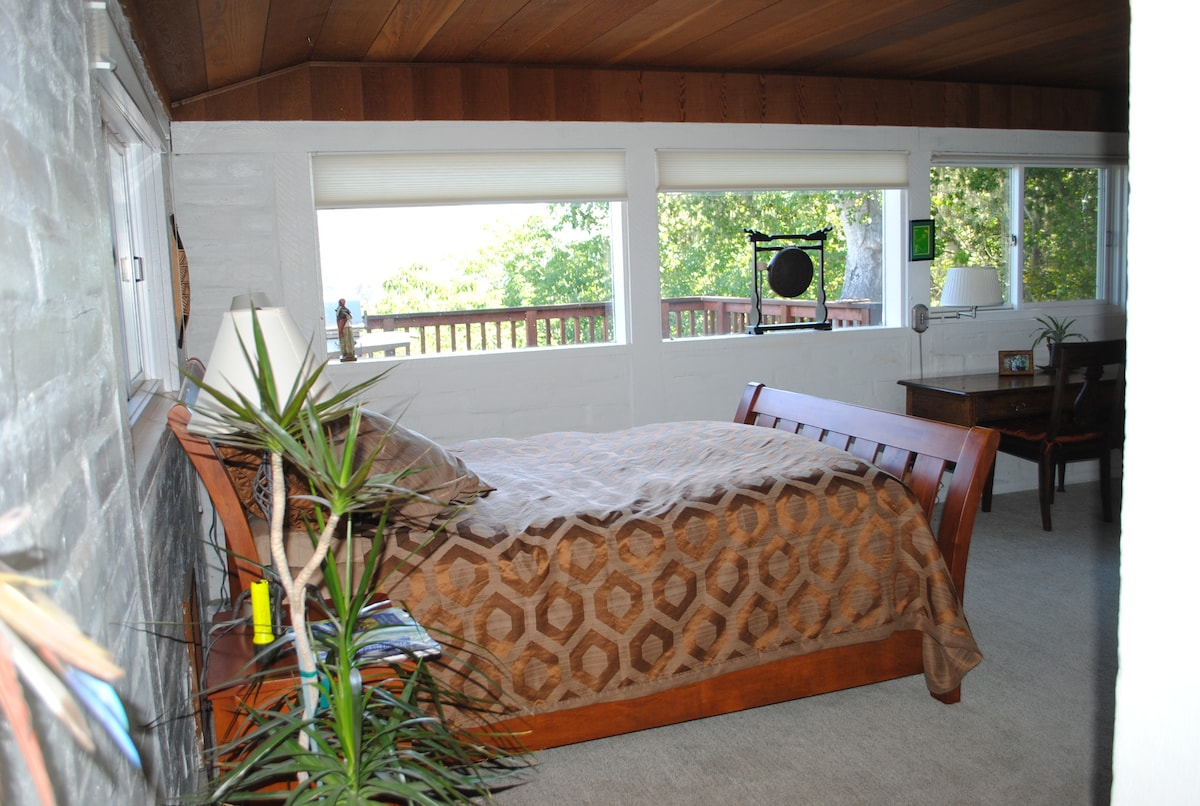The master bedroom has an adjoining bathroom and wood-burning fireplace.