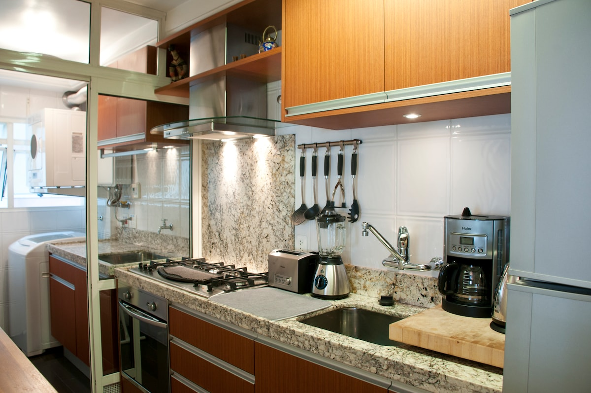 Modern kitchen and service area, with washer and dryer.  Kitchen has gas burners, electric grill, gas oven and oven grill.  Appliances of all sorts.