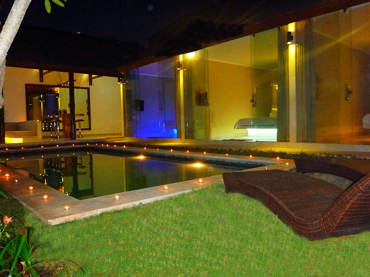 From the front door view into the custom lighting bedrooms at night. In distance living room and bar area.