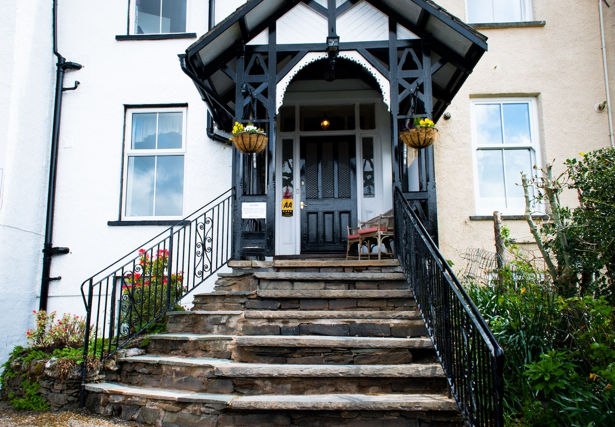 Welcome to our guest house in the English Lake District National Park. Blenheim Lodge was built in 1868 and here you can see Lakeland stone steps leading up to our front door. We are recognised by the Automobile Association as having 4 stars.