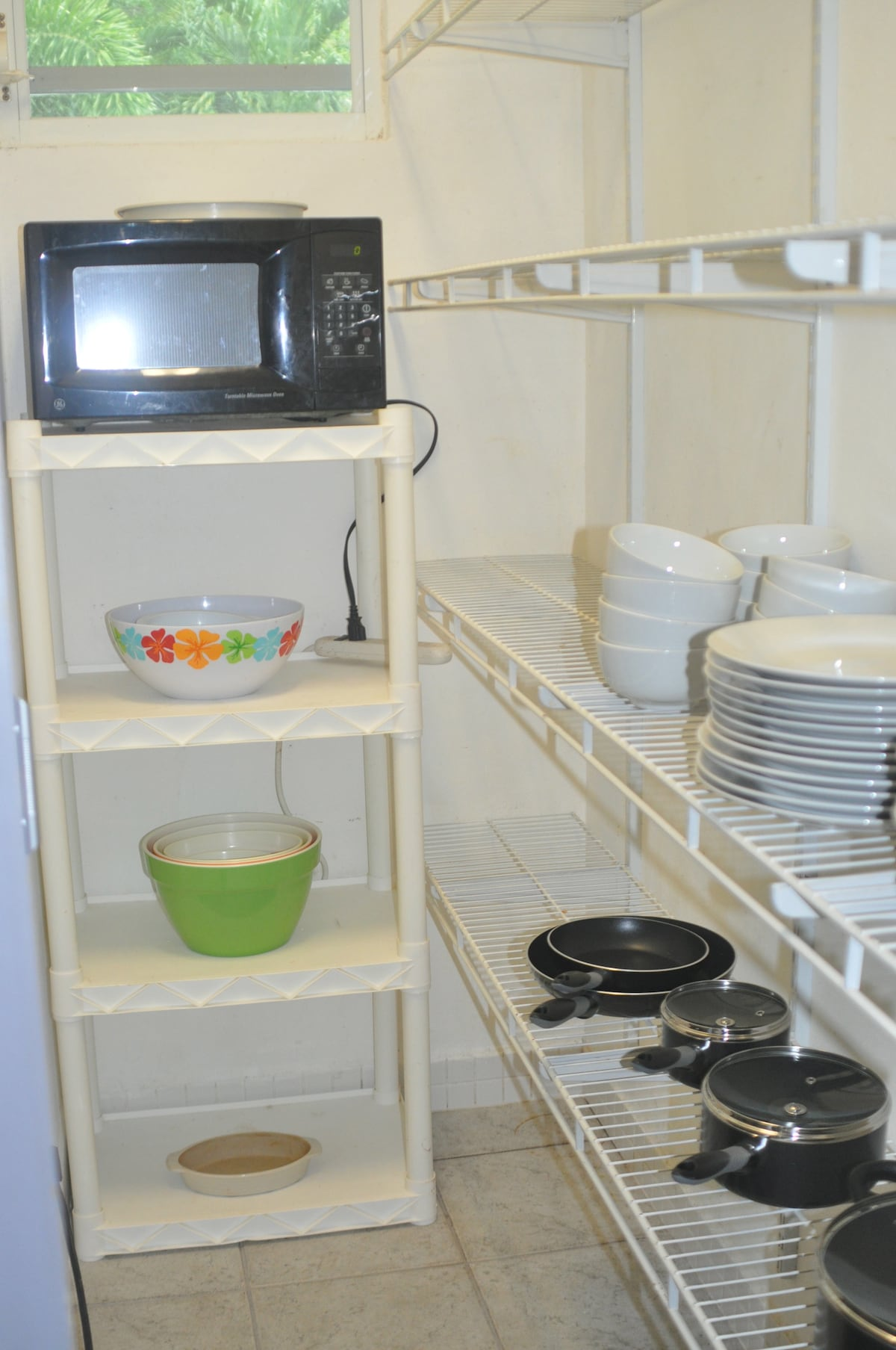 Fully stocked pantry with plates, bowls, pots and pans and a microwave
