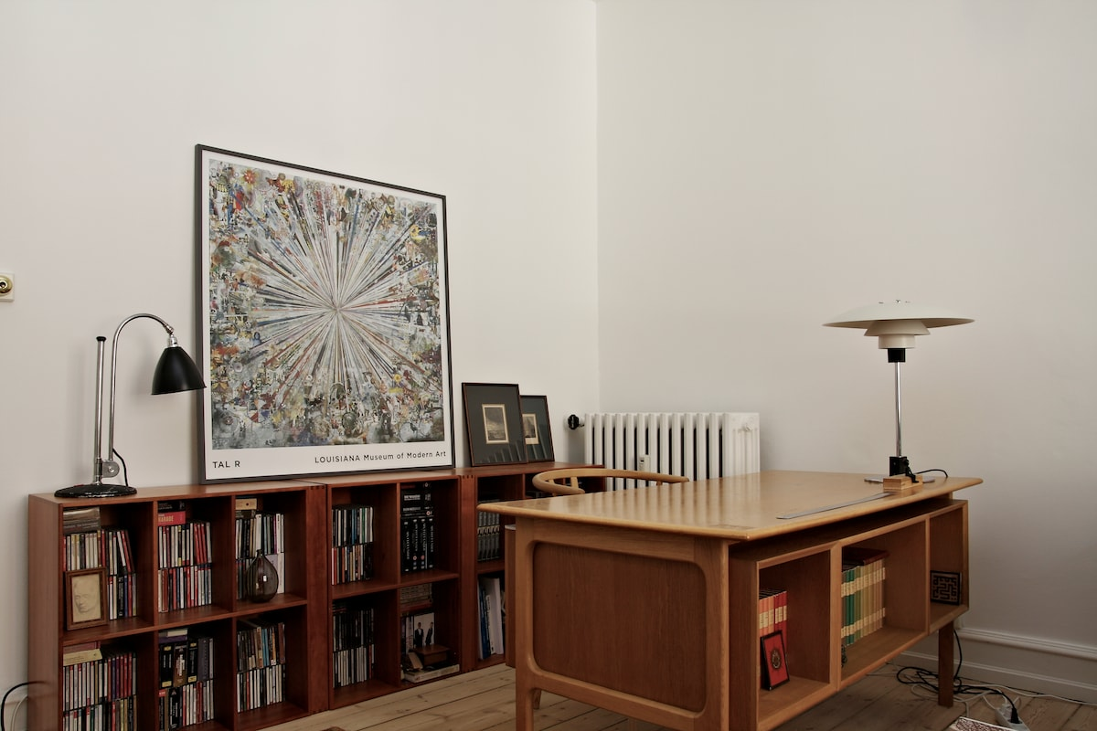 Desk area in sitting room. The flat is furnished with Danish design icons, from chairs to lamps and art.