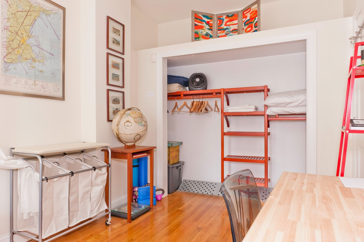 The guest bedroom has a large closet and vintage travel decor.