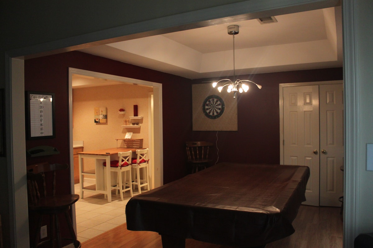 Pool table and dart board with laundry room behind doors