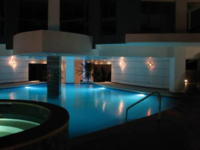 Swimming pool at night from the other end, Jacuzzi in the forefront