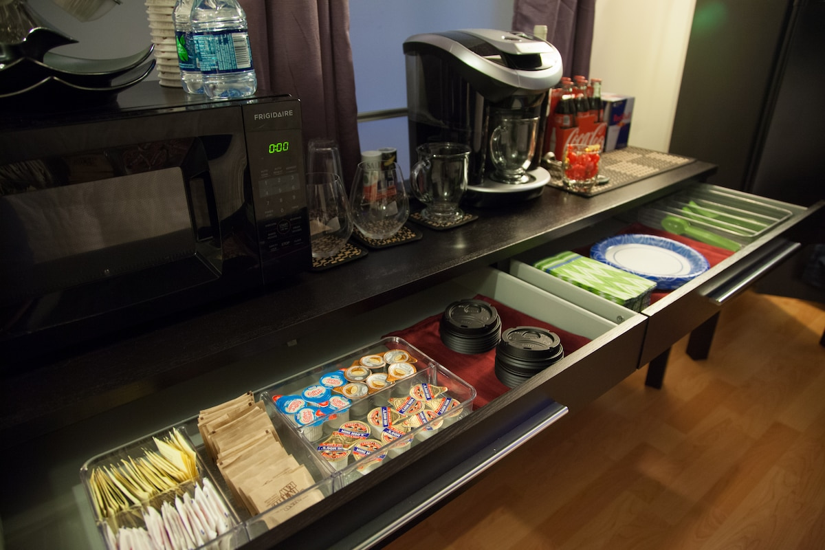 Fully stocked with sugars, half and half, flavored creamers, plasticware, paper plates, napkins and to go cups.