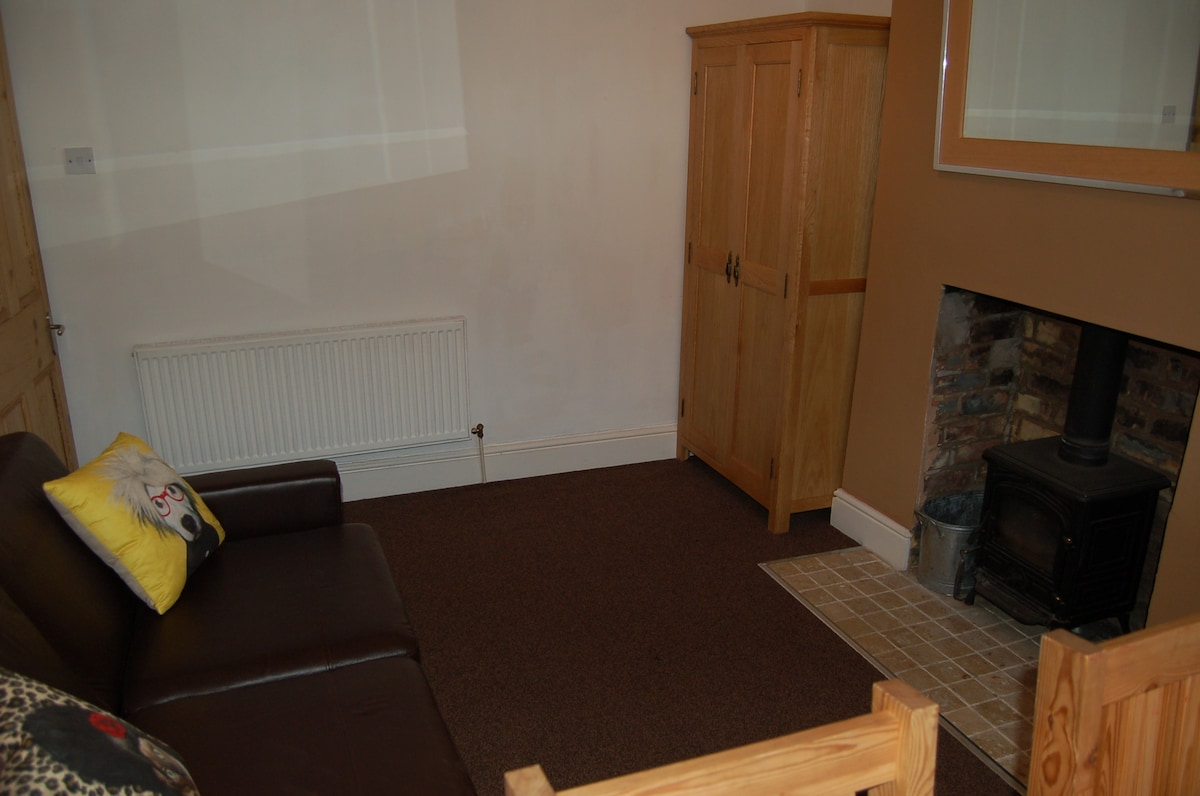 Alternative view of bedroom, with oak wardrobe and woodburning stove