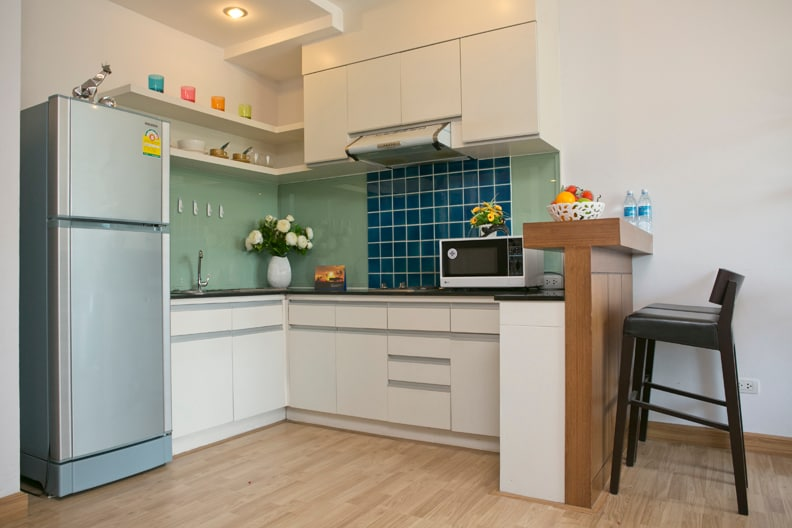 Modern kitchen complete with fridge, sink, stove and microwave oven.