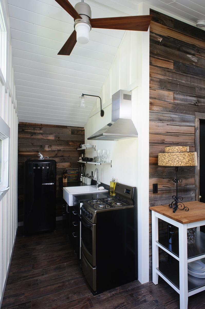Great european kitchen featuring barn board and a black Smeg refrigerator.
