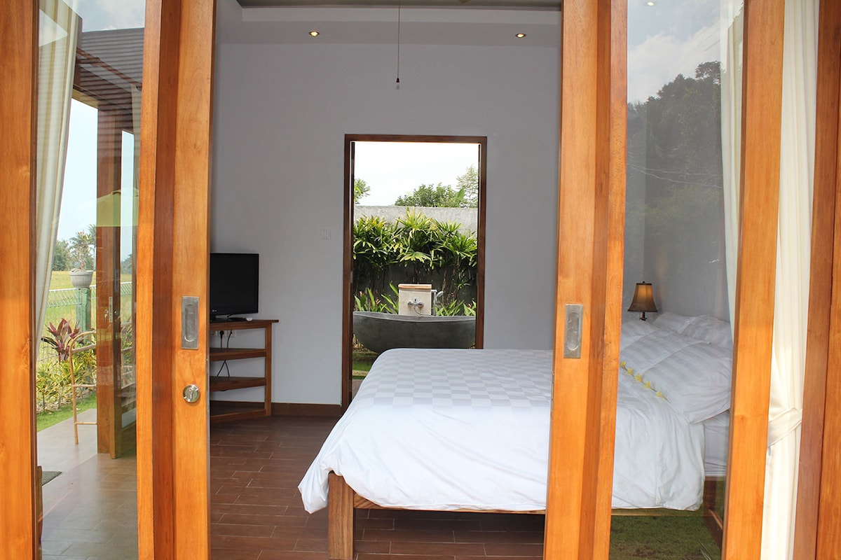 Another view of the guesthouse where you can see through to the outdoor bathroom, tub and gardens.