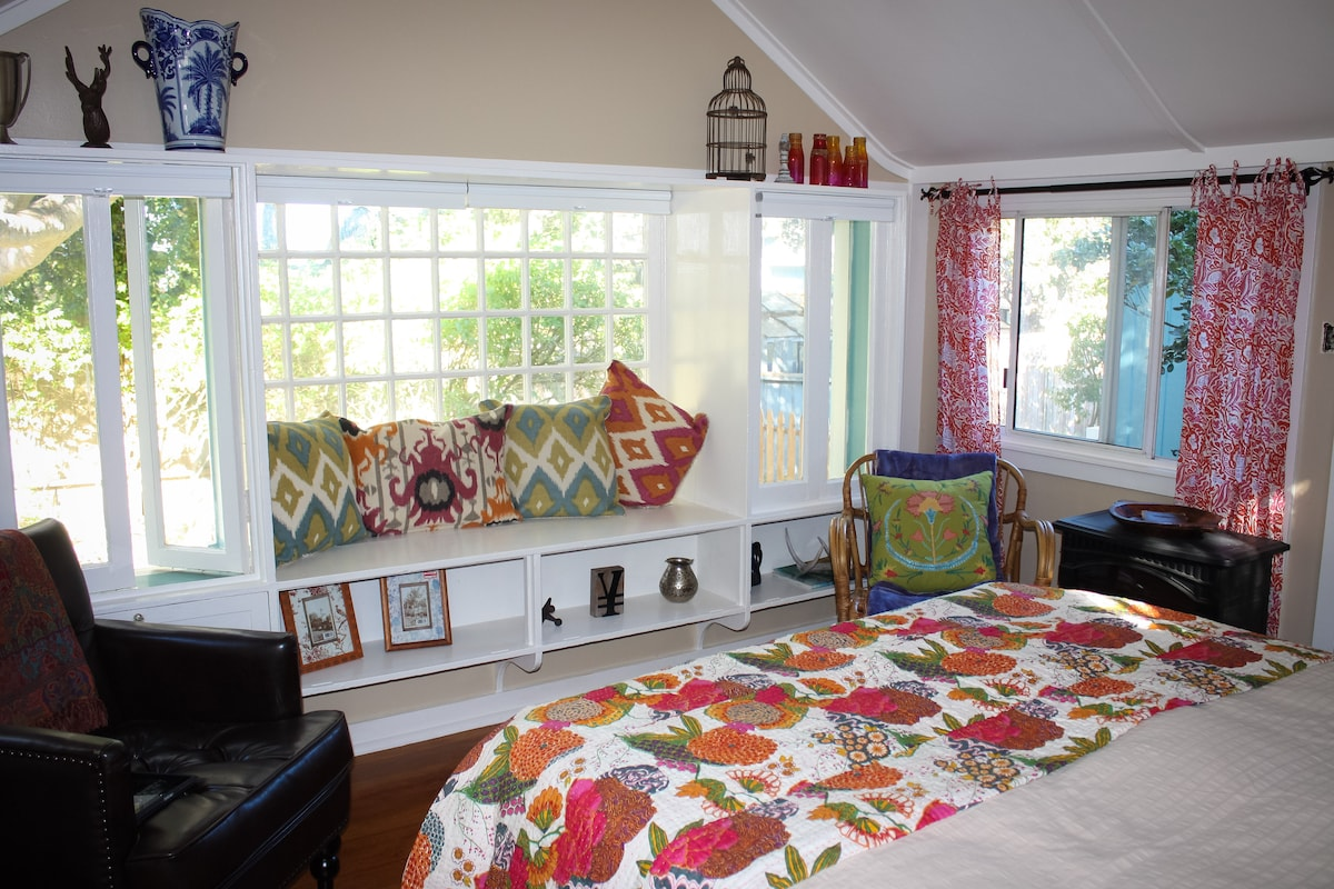 The his and her sitting area in front of the large picture window overlooking the garden.