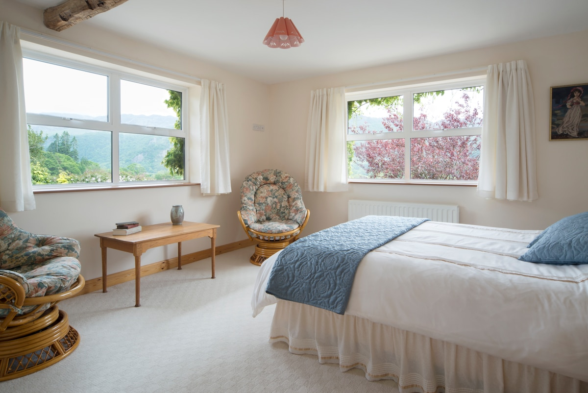The bedroom is spacious, with a king size bed, comfy rocking arm chairs, a separate dressing room area and stunning views.