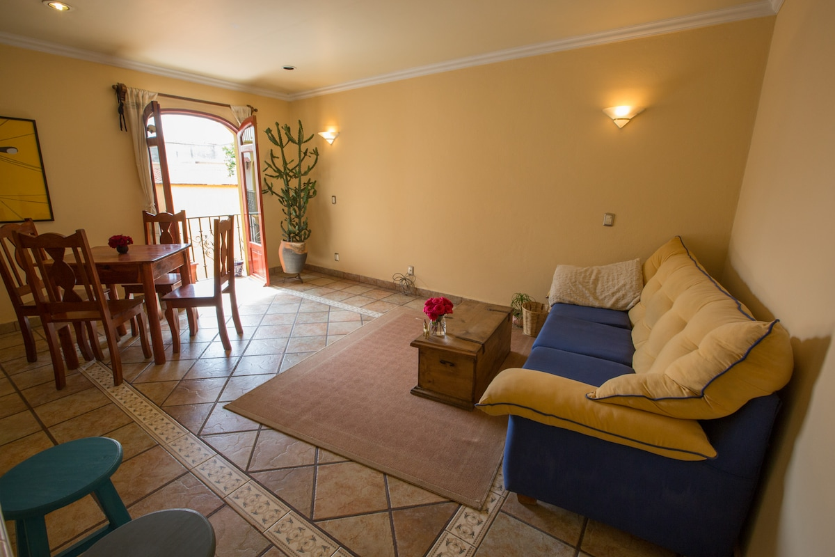 Main room, open living room & dining area with views of the courtyard from the balcony