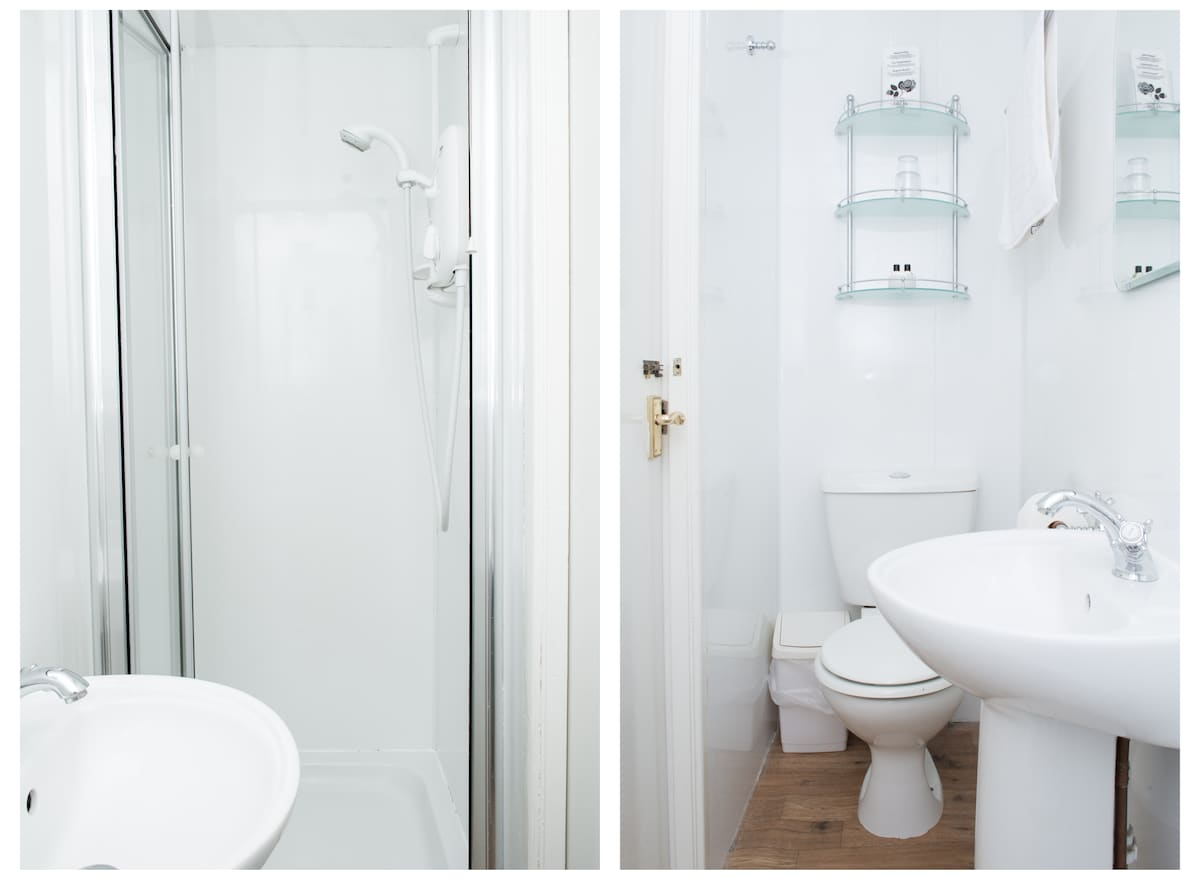 A small shower en-suite in The Coniston offers all the usual amenities, such as a toilet, sink, shelves and hooks, overhead shaver light and socket, and a shower cubicle with electric shower.