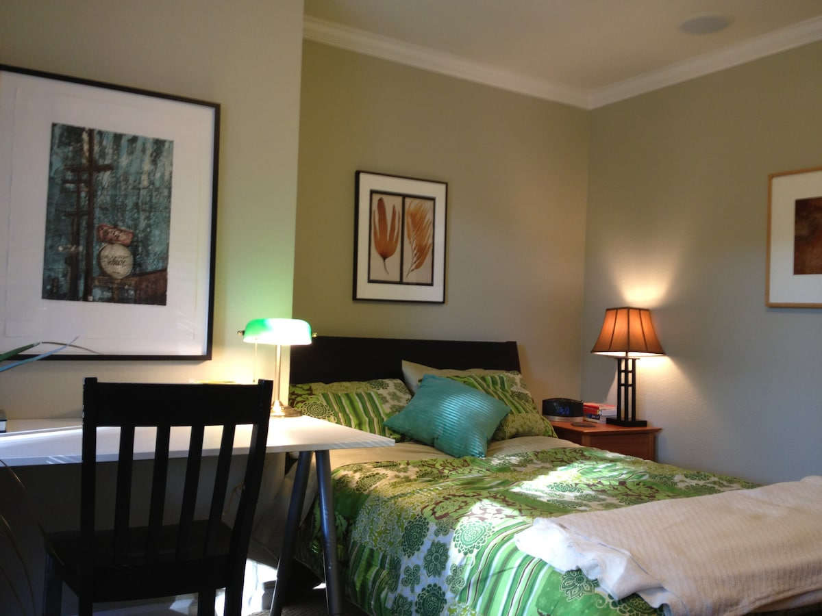 Bedroom with double bed, desk, dresser, easy chair, side table.  Closet is in the hallway