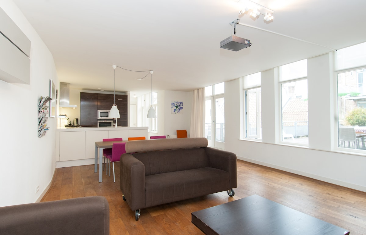 Large living room with fully equipped kitchen, comfy sofas, a large dining table and a projector for watching dvd's.