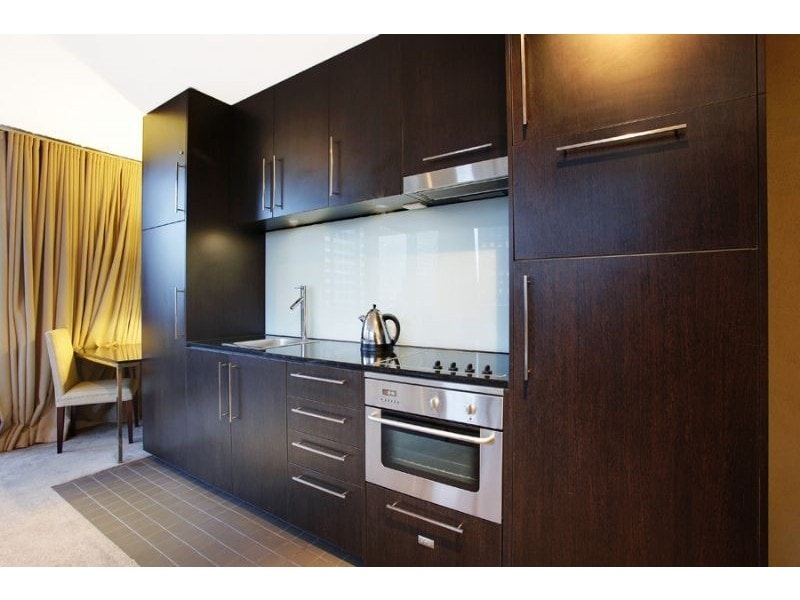 Kitchen with electric stove top, oven, dishwasher, toaster and kettle (in cupboard), microwave oven and fridge