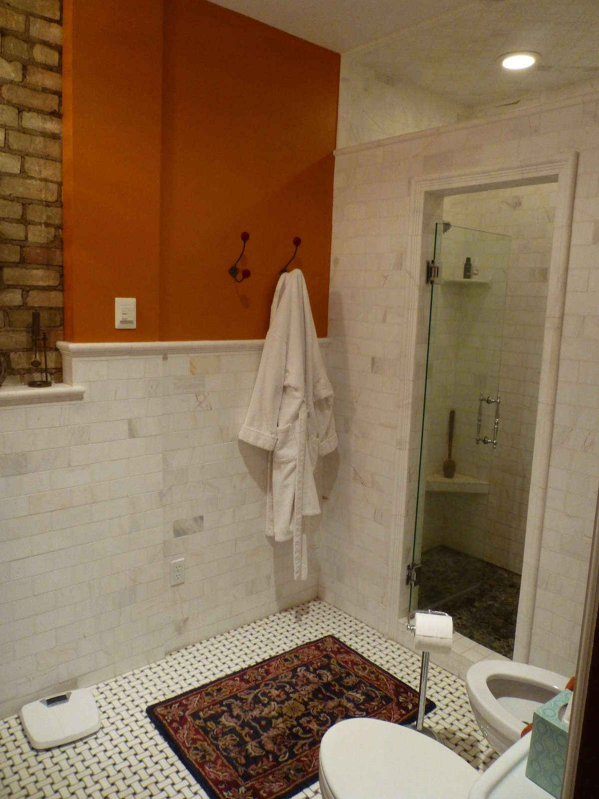 Bathroom includes double shower for two, featuring custom stone floor.