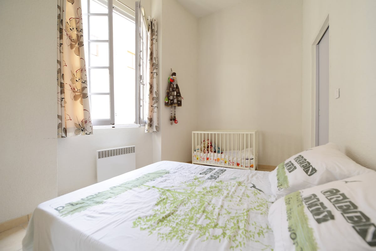 Bedroom with double bed and cot. Double windows to street below