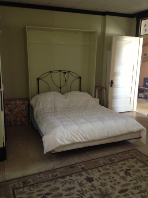 Queen Murphy Bed and door to hallway and stairs down to street level.