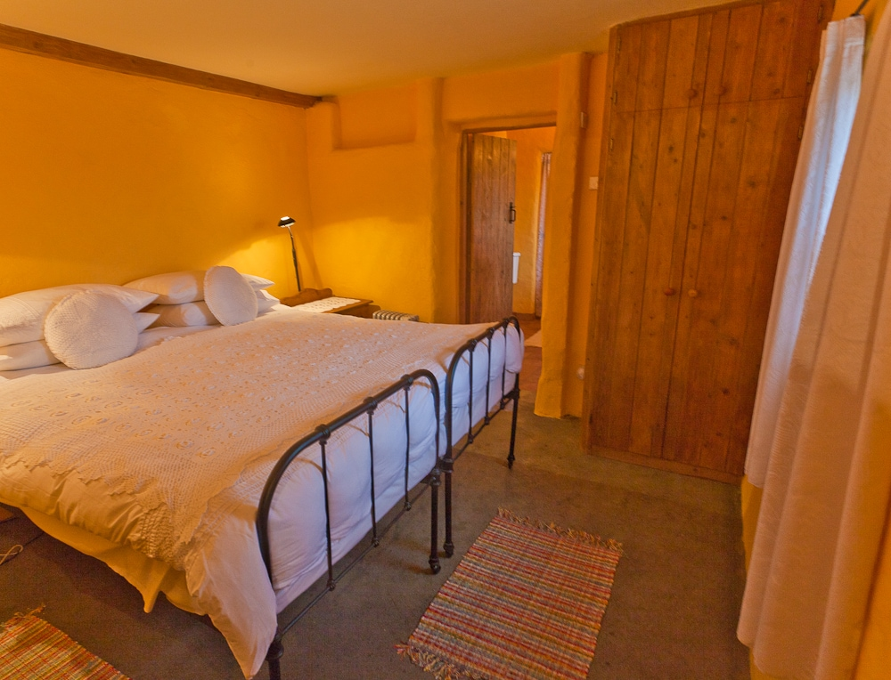 Ensuite bedroom with traditional cast iron, king-size bed and underfloor heating