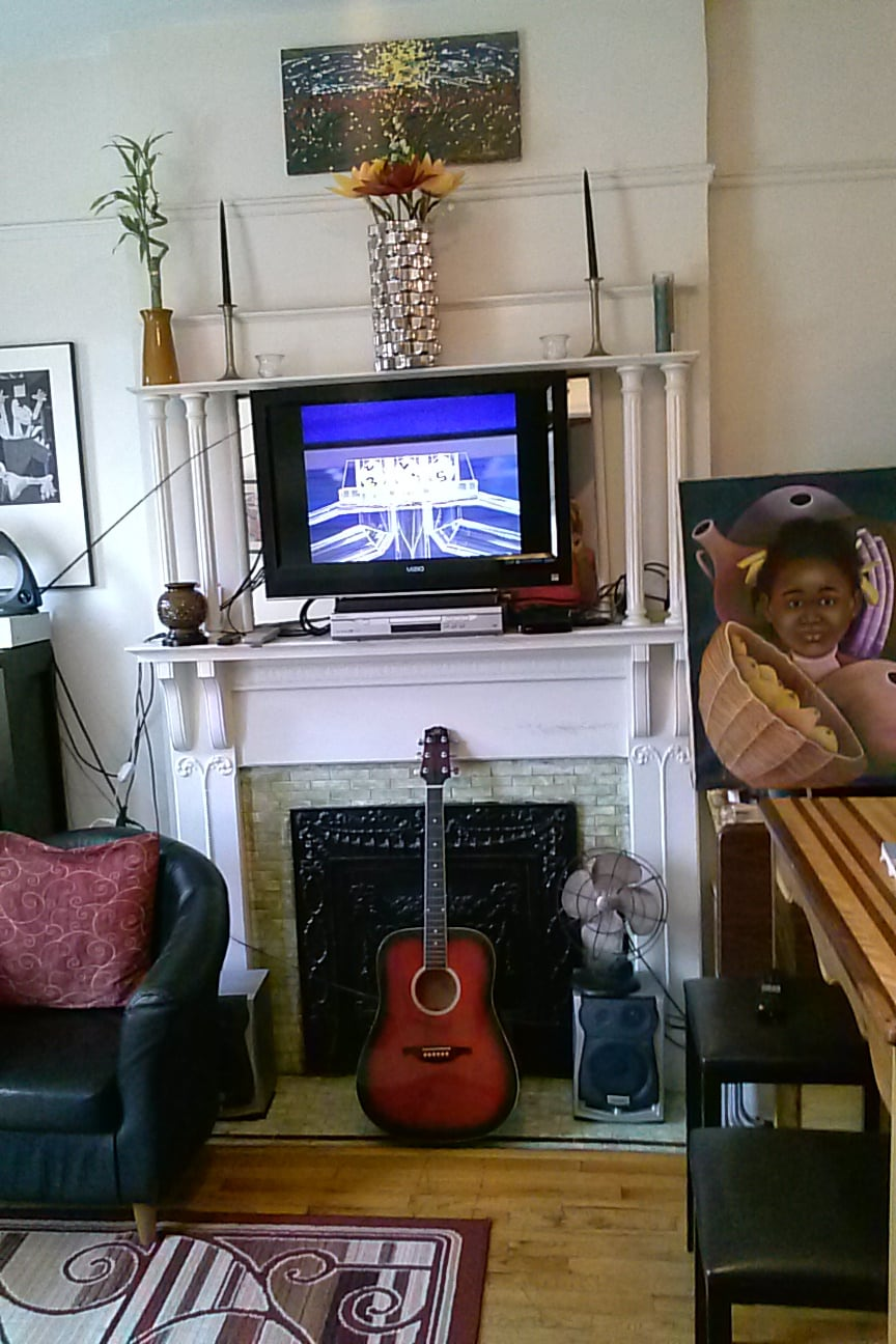T.V. and DVD above the fireplace, and the guitar my father gave me- home!