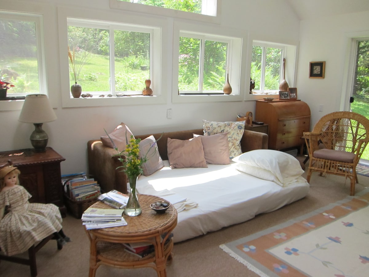 Sunny sitting room with bed made up