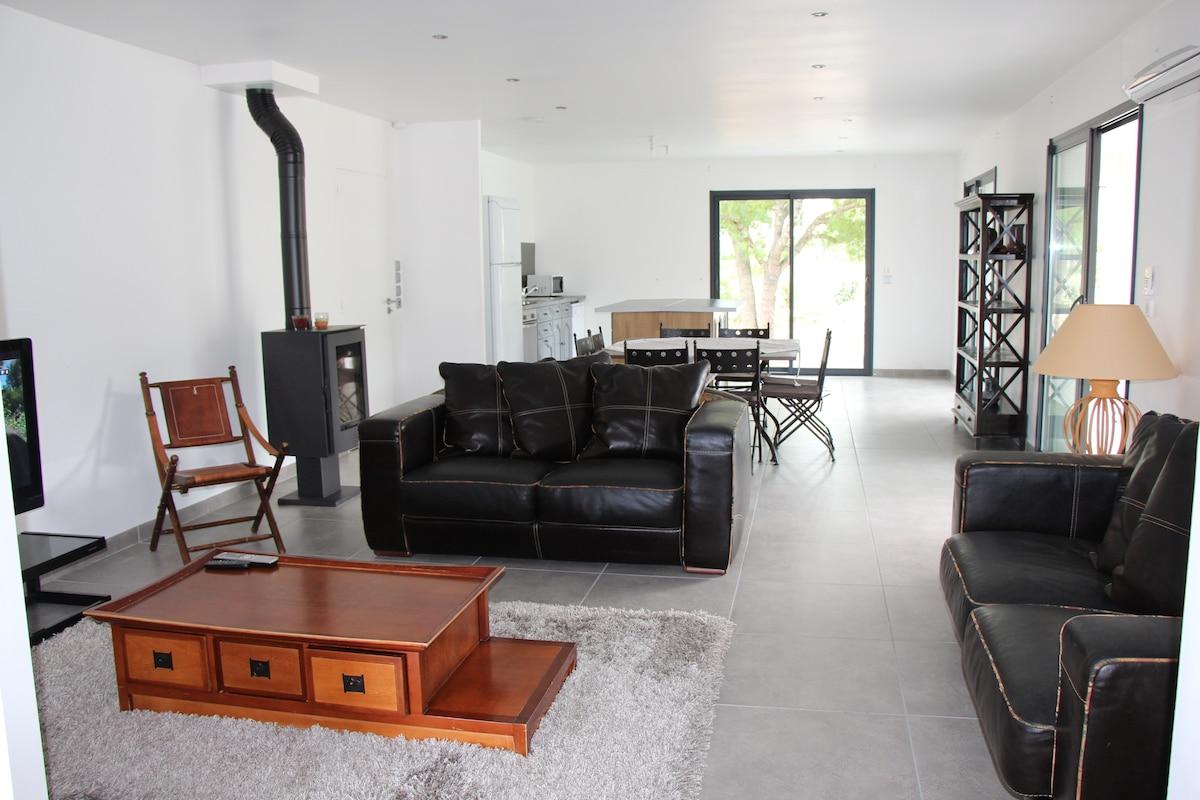 Salon séjour avec sa cuisine américaine au fond, 3 grandes baies coulissantes donnent accès au jardin