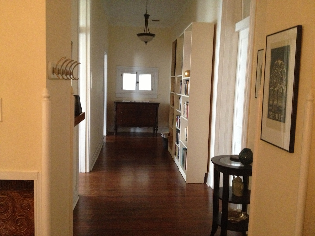 The hallway with bedrooms and bathroom on right, living room and kitchen on left. Three bookcases are filled with novels for your leisure reading.