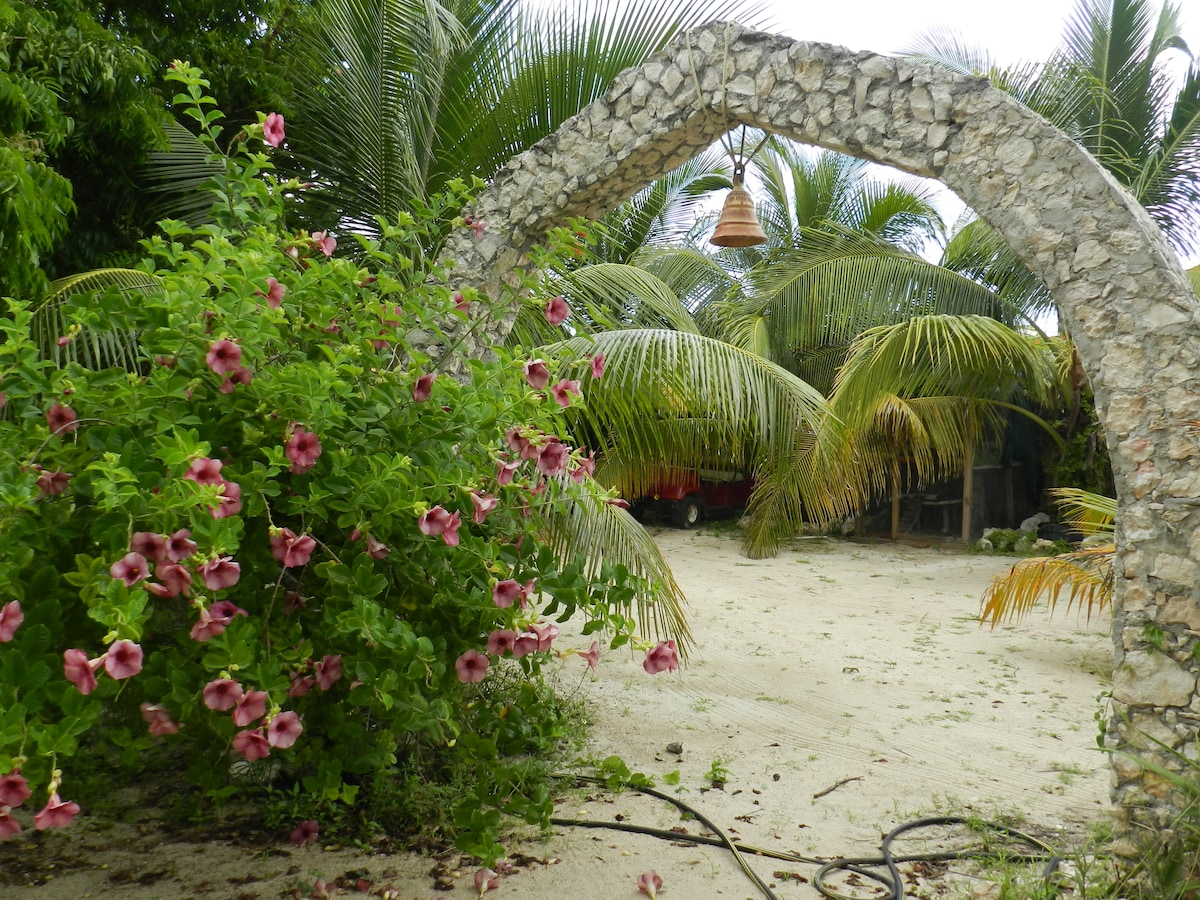 Archway leading from pool/coconut forest to the parking area.