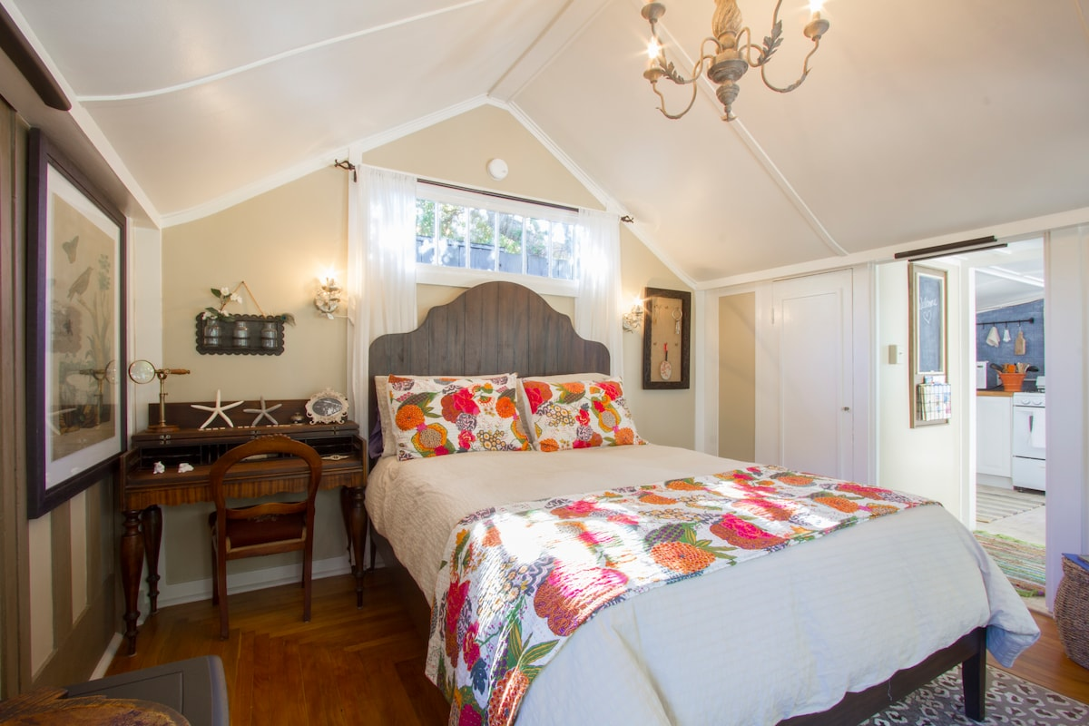 The romantic queen size bed and antique writing desk with views into the kitchen.