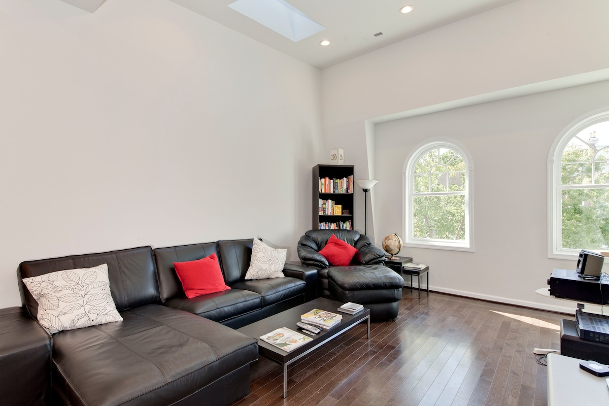 Living room with a sectional sofa and a chaise. The skylights make the property bright and airy and the vaulted ceilings give it an interesting architectural style.