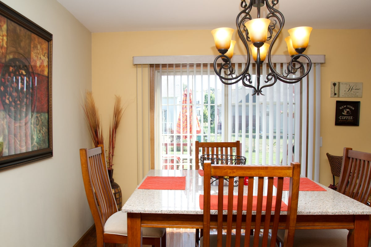 Kitchen table features stone top and padded chairs for your comfort; sliding glass doors lead to the back patio and yard