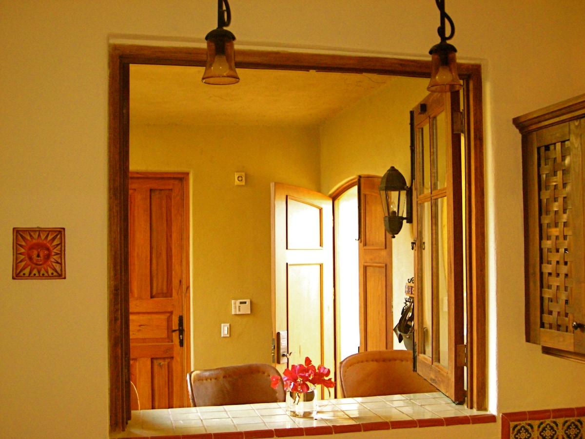 Warm colours of kitchen window bar seats off front door.